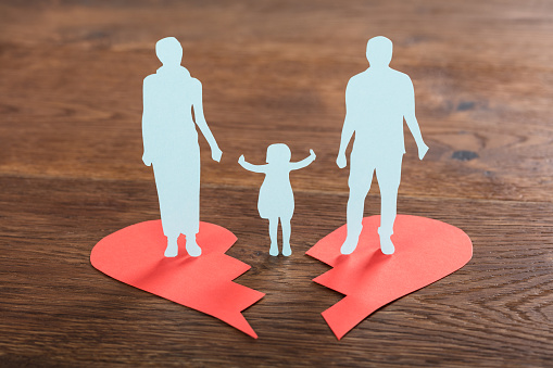 Paper cutouts of a child split between two adults