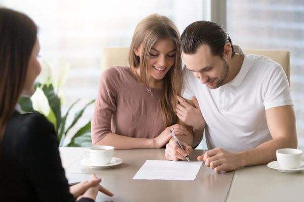Young couple signing prenuptial agreement
