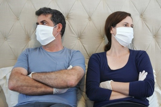 A married couple lie in bed, upset with each other, while wearing medical face masks.